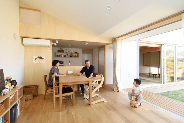 ダイニングとキッチン。庭を挟んで和室が見える: 加藤淳一級建築士事務所が手掛けたダイニングです。