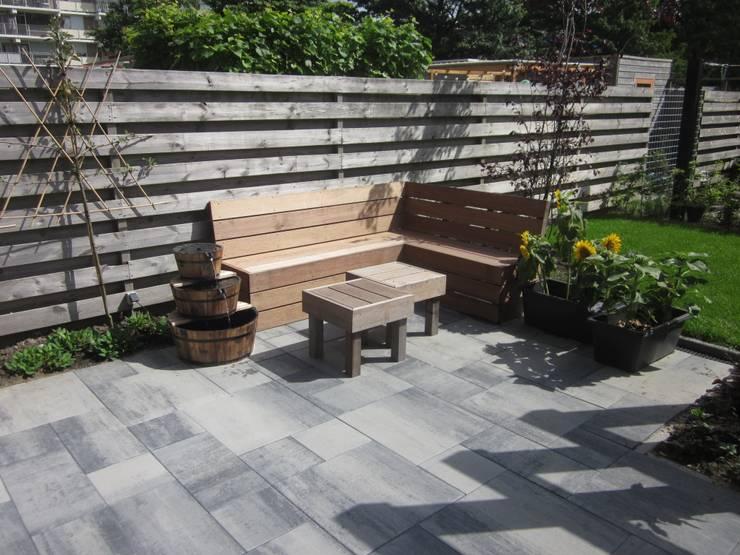 Zelfgemaakte zithoekbank die aangekleed met kussen zeker een mooie plek is in de tuin om te genieten.:  Terras door Van Dijk Tuinen Groningen