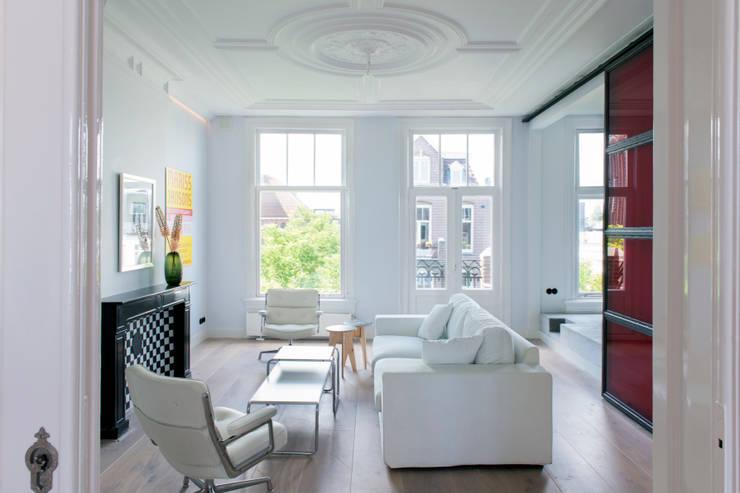 lichte huiskamer met ornamenten plafond:  Woonkamer door IJzersterk interieurontwerp, Modern
