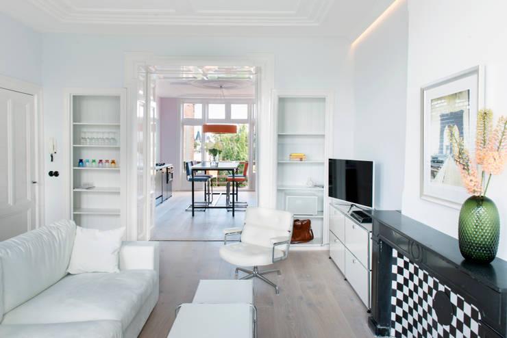 lichte huiskamer met ornamenten plafond:  Woonkamer door IJzersterk interieurontwerp, Industrieel