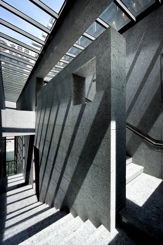 外立面石材延伸至天光投射下的公共梯間:   by Arcadian Design 冶鑄設計