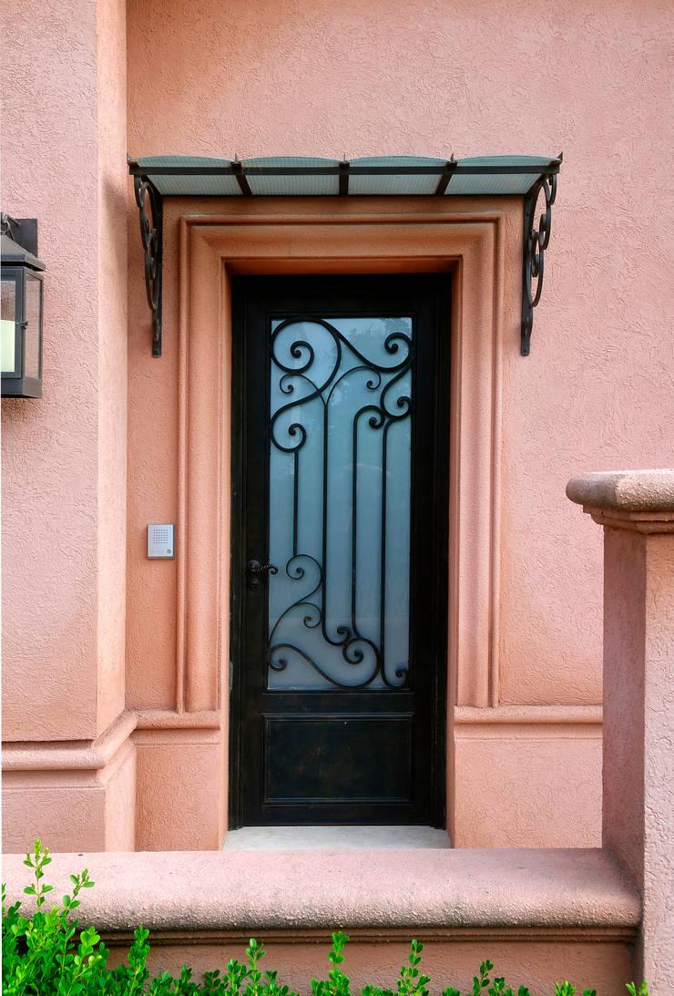 Alero y puerta de hierro forjado: Casas de estilo  por DEL HIERRO DESIGN,