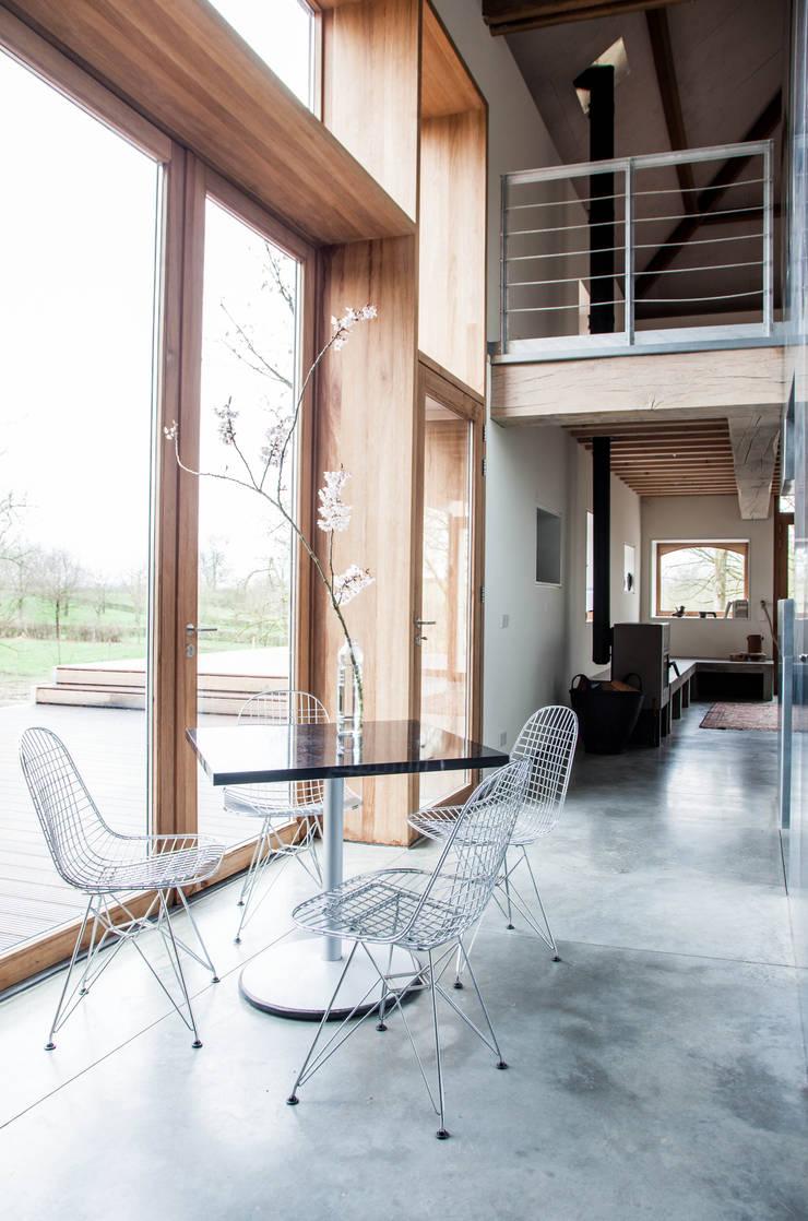 Interieur met grote houten kozijn en industriele betonnen gietvloer:  Eetkamer door JEANNE DEKKERS ARCHITECTUUR, Landelijk Beton