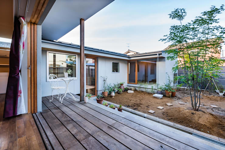 コの字の増築: 一級建築士事務所オブデザインが手掛けた庭です。