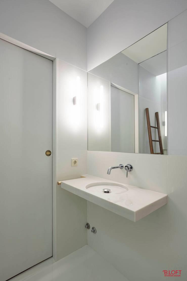 Vista geral lavatório e entrada: Casas de banho  por B.loft