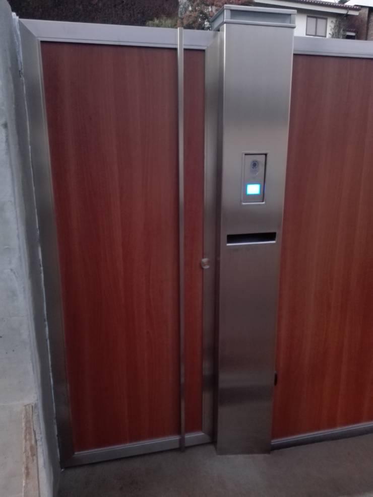 Portão de entrada Inox/madeira: Casas  por Jolucor