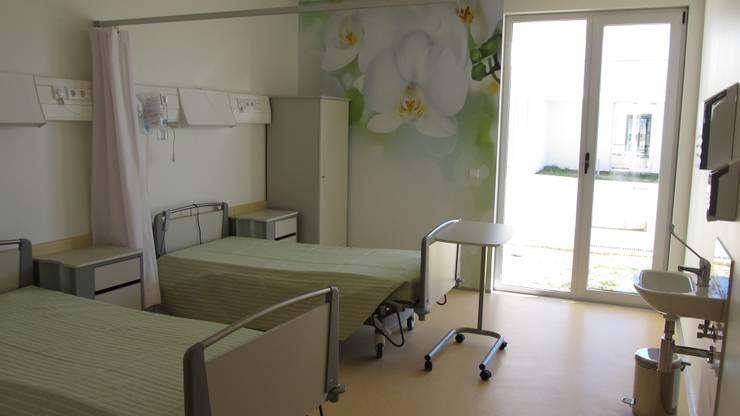 Unidade de Cuidados Continuados de Coruche: Quartos  por MARIA ILHARCO DE MOURA ARQUITETURA DE INTERIORES E DECORAÇÃO,