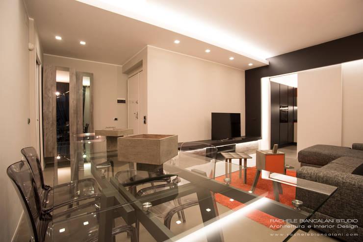 Living con pavimento in resina spatolata, grigio e tavolo in cristallo: Soggiorno in stile  di Rachele Biancalani Studio