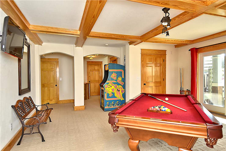 game room with pool table and arcade: modern Media room by Outer Banks Renovation & Construction