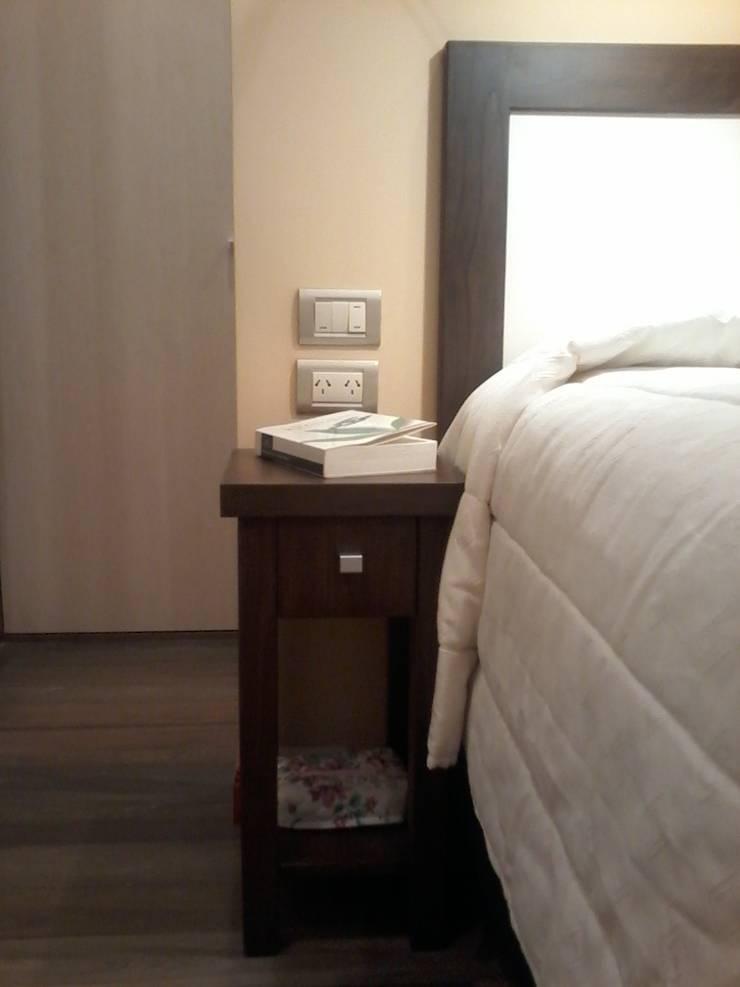 Detalle del mobiliario del dormitorio, resuelto en madera lustrada tono nogal, con respaldo de cama tipo cuadro con tablero de melamina simil lino claro.: Dormitorios de estilo  por D&C Interiores,