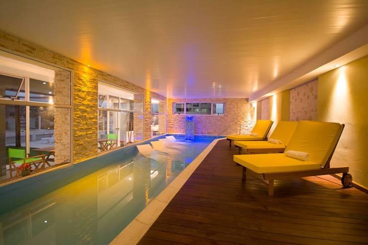 Detalle del deck del área de relax contiguo a la pileta. Se aprecia en el remate el totem con cascada.: Hoteles de estilo  por D&C Interiores,