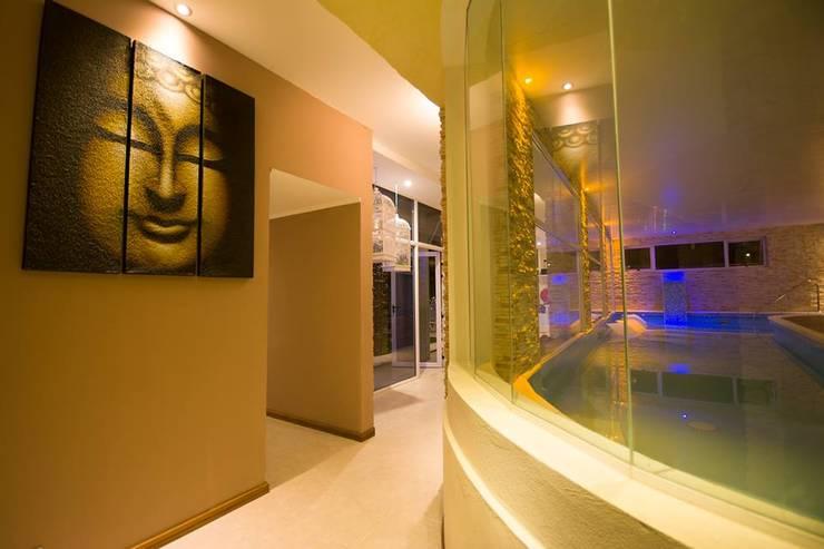 Vista del ingreso al spa. Se observa el muro curvo y vidriado del hidromasajes.: Hoteles de estilo  por D&C Interiores,