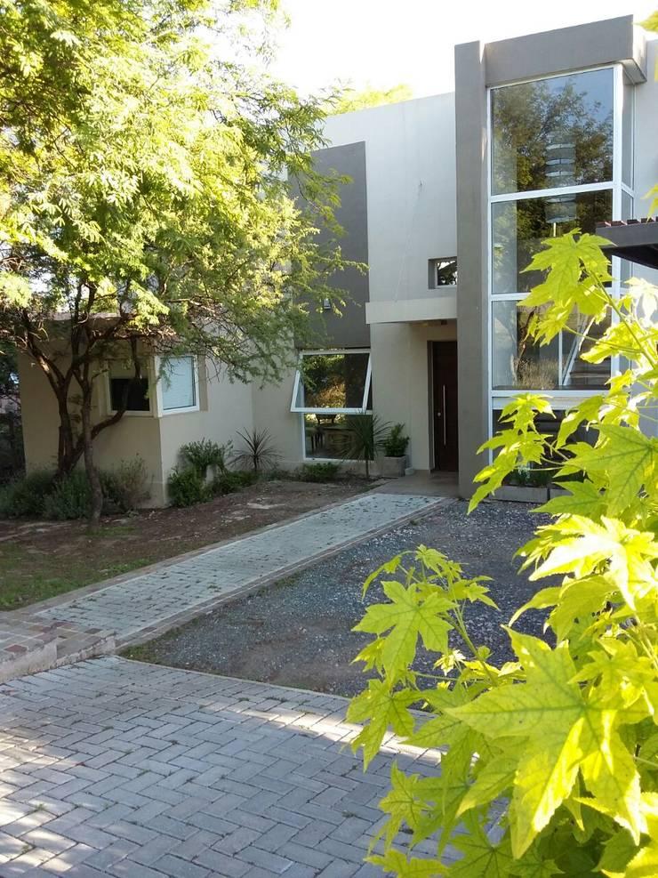 ingreso peatonal y vehicular : Casas de estilo  por LOSADA ARQUITECTURA,Moderno Piedra