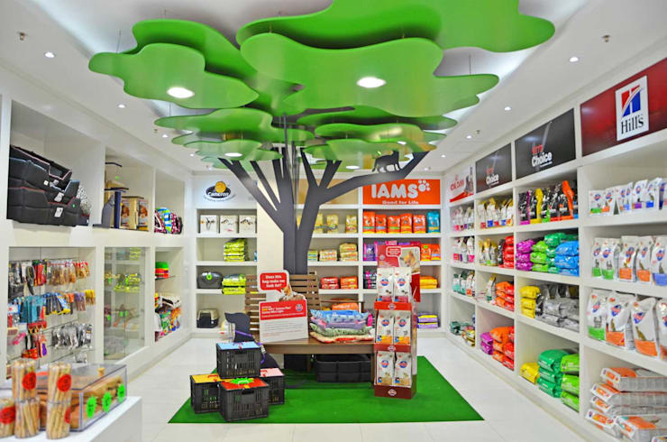 Shop interior with 'park themed' tree, bench & animals:  Commercial Spaces by Till Manecke:Architect, Eclectic