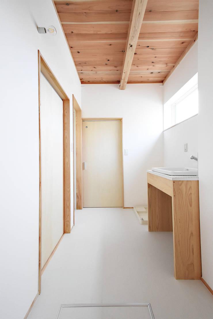 白を基調とした清潔感を感じさせる洗面脱衣室: 合同会社negla設計室が手掛けた浴室です。,