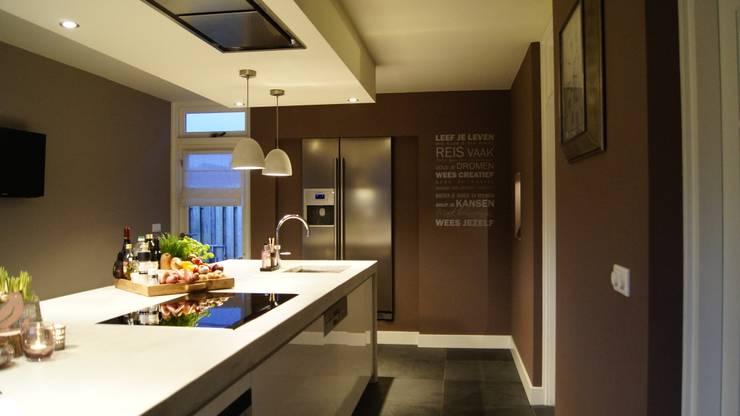 Moderne woonkeuken met kookeiland, quooker en Amerikaanse koelkast in nis:  Keuken door Langens & Langens BV, Modern
