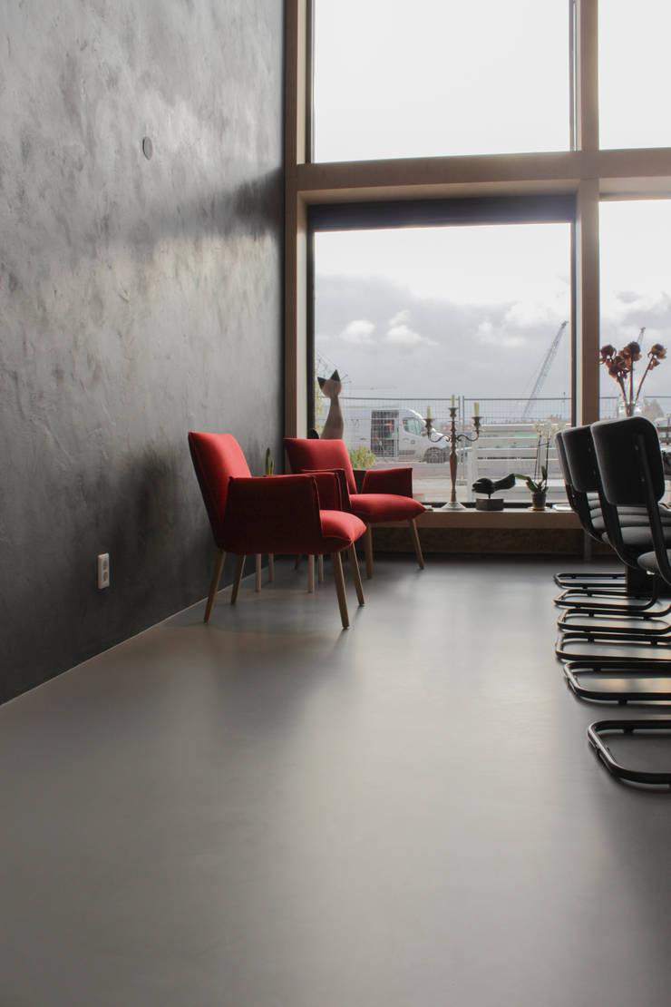 Betonlook gietvloer in combinatie met een minimalistisch interieur:  Muren & vloeren door Motion Gietvloeren