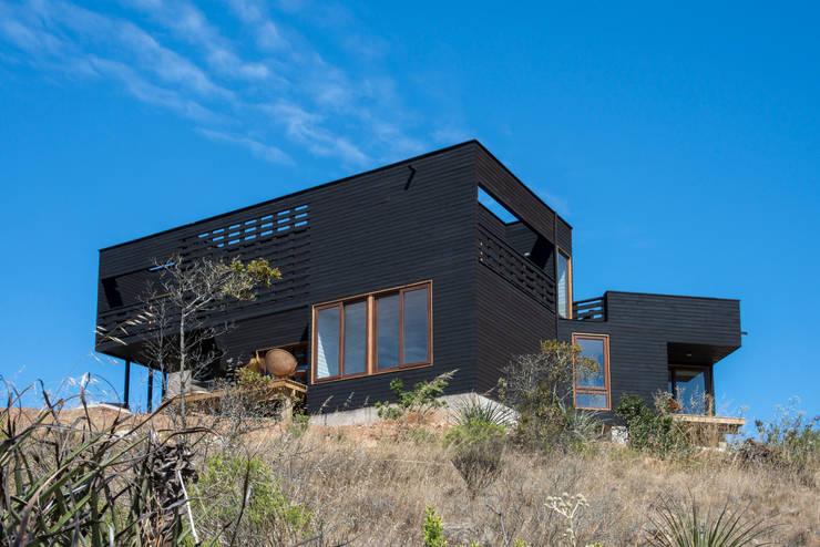 vista frontal, fachada suroriente: Casas de estilo rústico por Thomas Löwenstein arquitecto