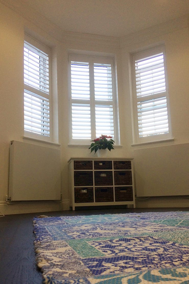 Bedroom shutters for bay windows:  Bedroom by Plantation Shutters Ltd