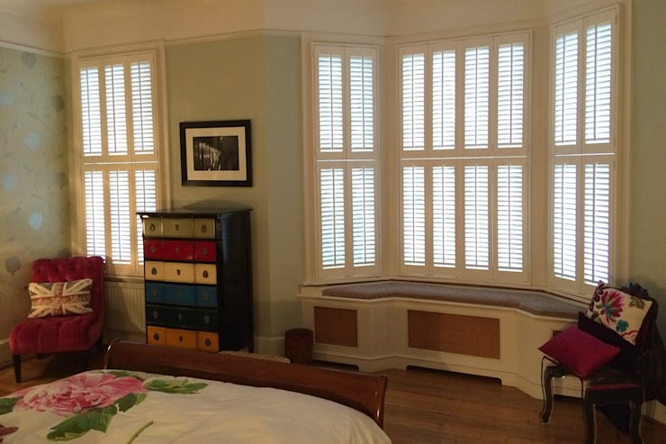 Tier on tier shutters for bay windows:  Bedroom by Plantation Shutters Ltd