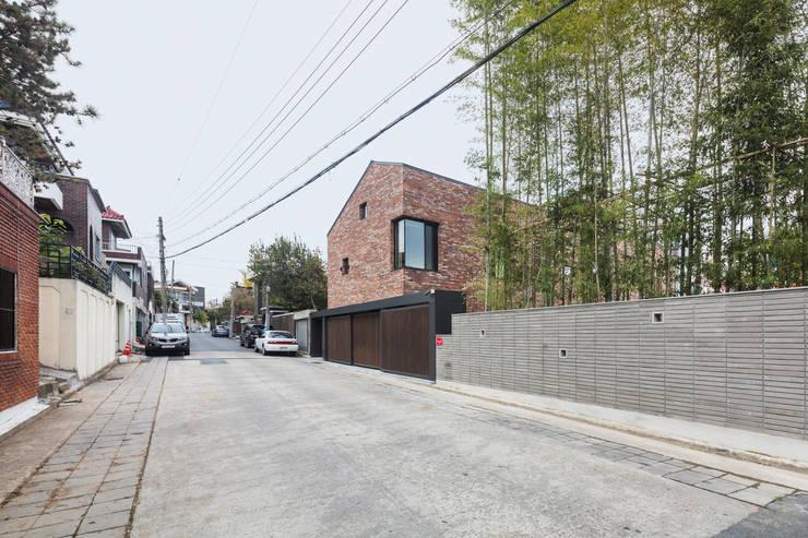 동측 도로에서 집을 바라보다: (주)건축사사무소 모도건축의  주택