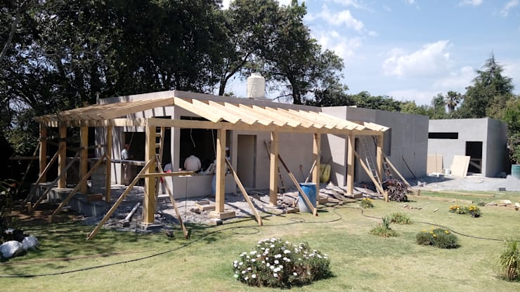 Vista de fachada principal con pergolado de madera en proceso de colocación.: Casas de estilo  por taller garcia arquitectura integral