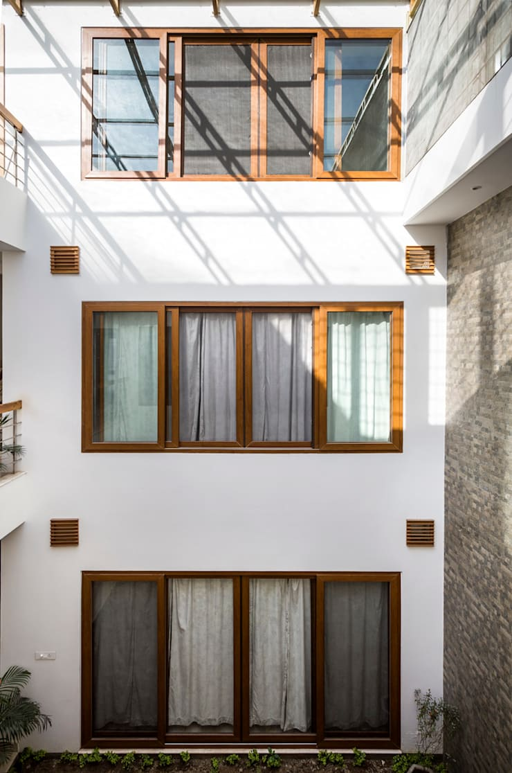 Bedroom Windows opening into the courtyard:  Windows by Manuj Agarwal Architects