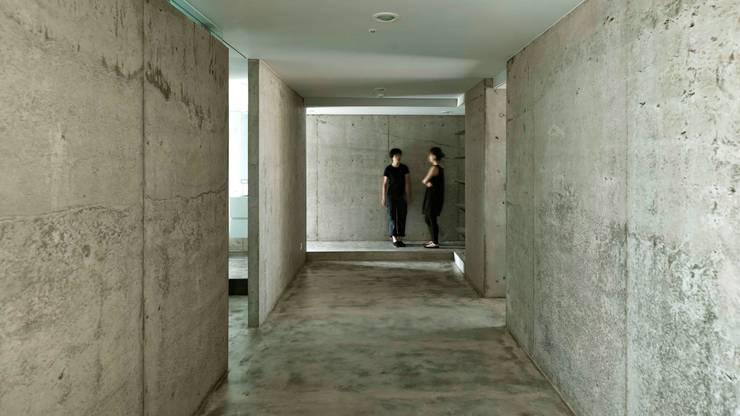 你被水泥的量體包圍?不,是被恰好的對流包圍。:  走廊 & 玄關 by 本晴設計