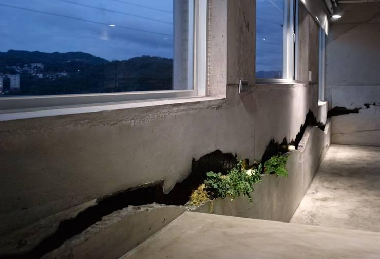 黑色裂縫像立體潑墨,也呼應了窗外匍匐山稜。:  走廊 & 玄關 by 本晴設計