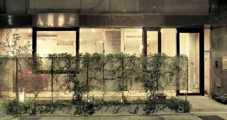 綠植爬滿金屬網邊界,使診間落地窗亦能維持必要的遮蔽感。:  診所 by 本晴設計