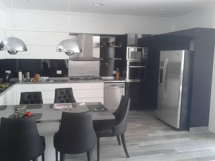 Cocina moderna minimalista, realizada en laca negra brillante , laca blanca semimate y mesadas y detalles de acero inoxidable.: Cocinas de estilo  por Flag equipamientos