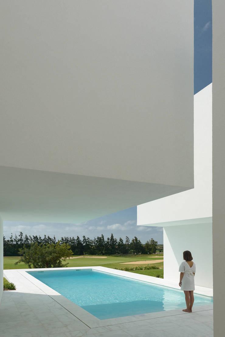 Entre dois Muros Brancos: Piscinas  por Corpo Atelier