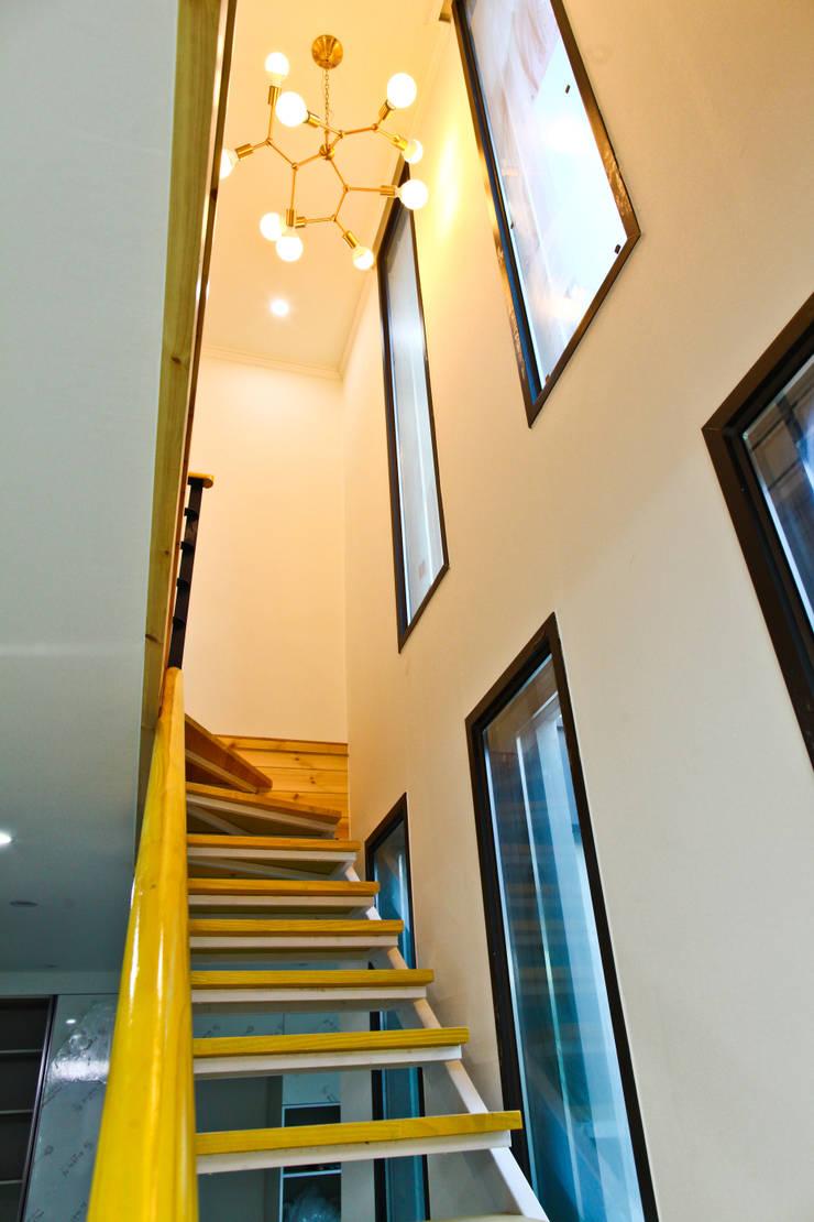직선의 미학을 보여주는 모던 전원주택: 한글주택(주)의  복도 & 현관