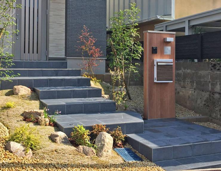 ダークカラーのタイルを貼った重厚感のあるアプローチに、木目調の機能門柱や郵便ポストでナチュラルモダンなエクテリア: 匠ガーデンが手掛けた家です。,モダン タイル