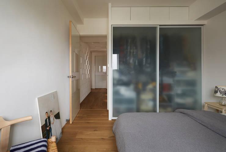或許不少人認為衣櫃內的收納應該遮蔽起來,但是通透的材質卻讓空間不顯狹小:  臥室 by 弘悅國際室內裝修有限公司