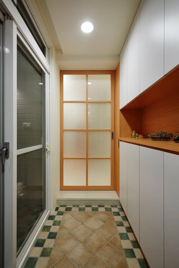 玄關對應著兩個入口,收納是一個部分,另一個部分是白色與木作的搭配:  走廊 & 玄關 by 弘悅國際室內裝修有限公司