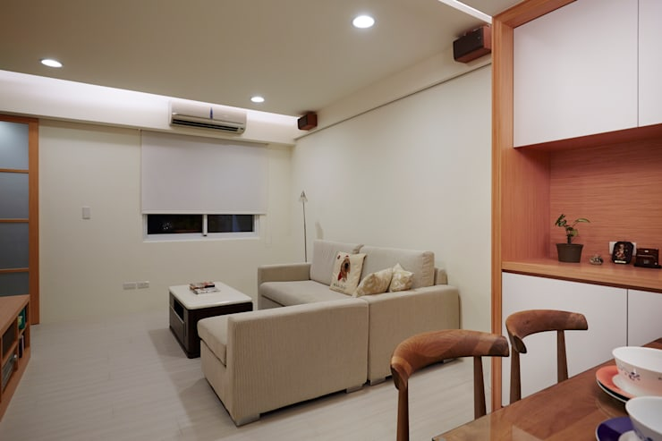 單層不大的空間儘量簡化用色避免造成擁擠的視覺焦點:  客廳 by 弘悅國際室內裝修有限公司