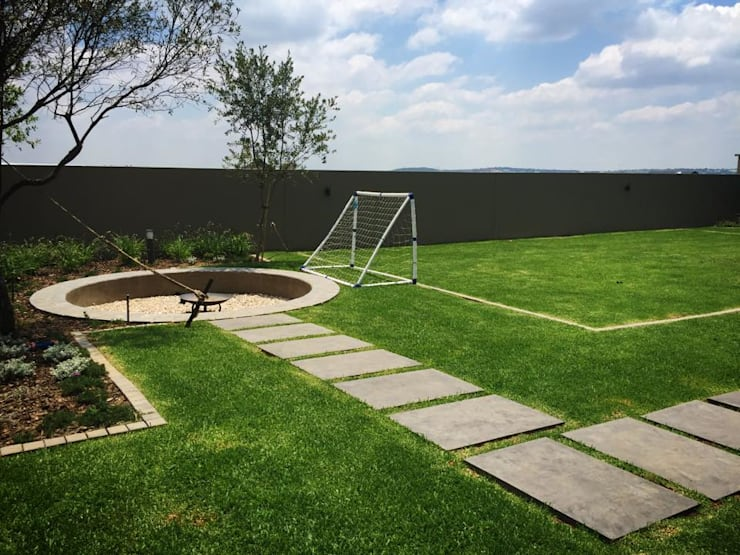 Fire pit and soccer pitch:  Garden by Acton Gardens