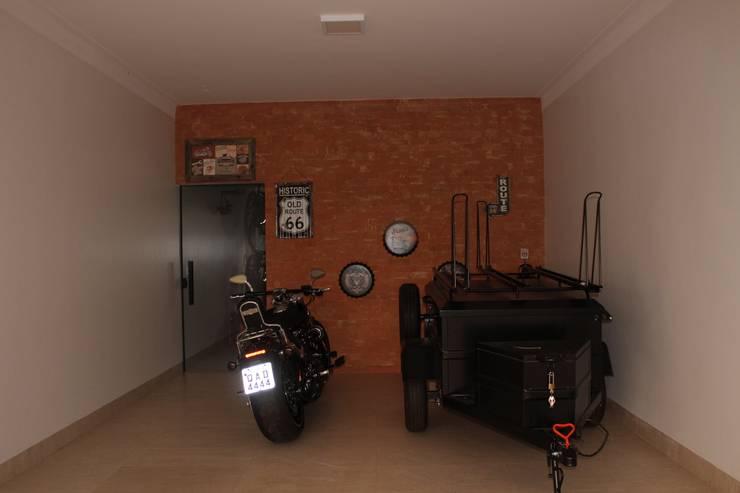 Garagem com pegada indutrial: Garagens e edículas modernas por Arquiteta Bianca Monteiro