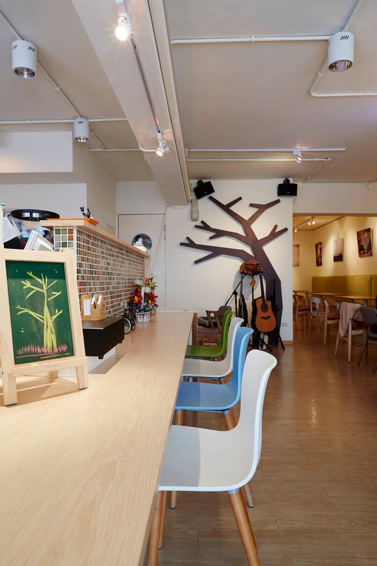 輕鬆的木色帶著北歐的風味,而背後的樹枝造型成為入眼的第一眼映像:  餐廳 by 弘悅國際室內裝修有限公司