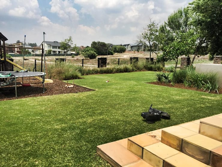 Clean lines and flow - family garden:  Garden by Acton Gardens