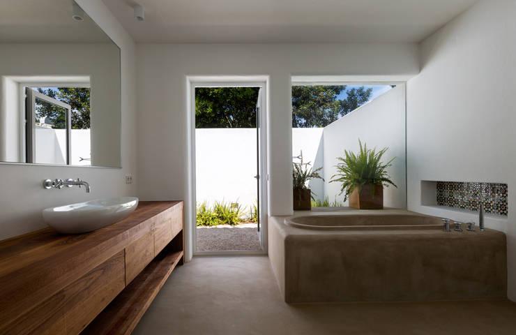 Bañera de hormigón y mueble de baño de madera con vistas al jardín.: Baños de estilo  de Alejandro Giménez Architects