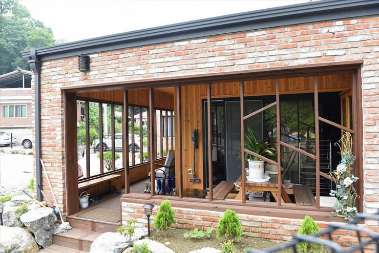 주택 현관 테라스: 한다움건설의  목조 주택