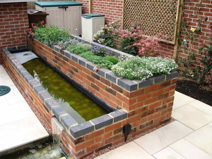 Raised bed and water feature 根據 Jane Harries Garden Designs 現代風 磚塊