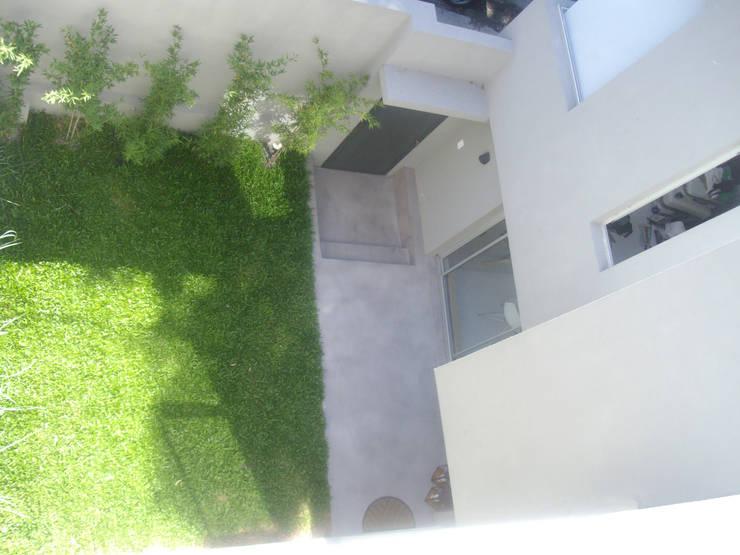 Patio de acceso.: Jardines en la fachada de estilo  por NG Estudio,