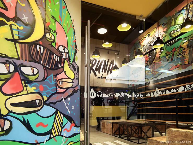 Detalle de graffiti en el ingreso: Oficinas y Tiendas de estilo  por SXL ARQUITECTOS,