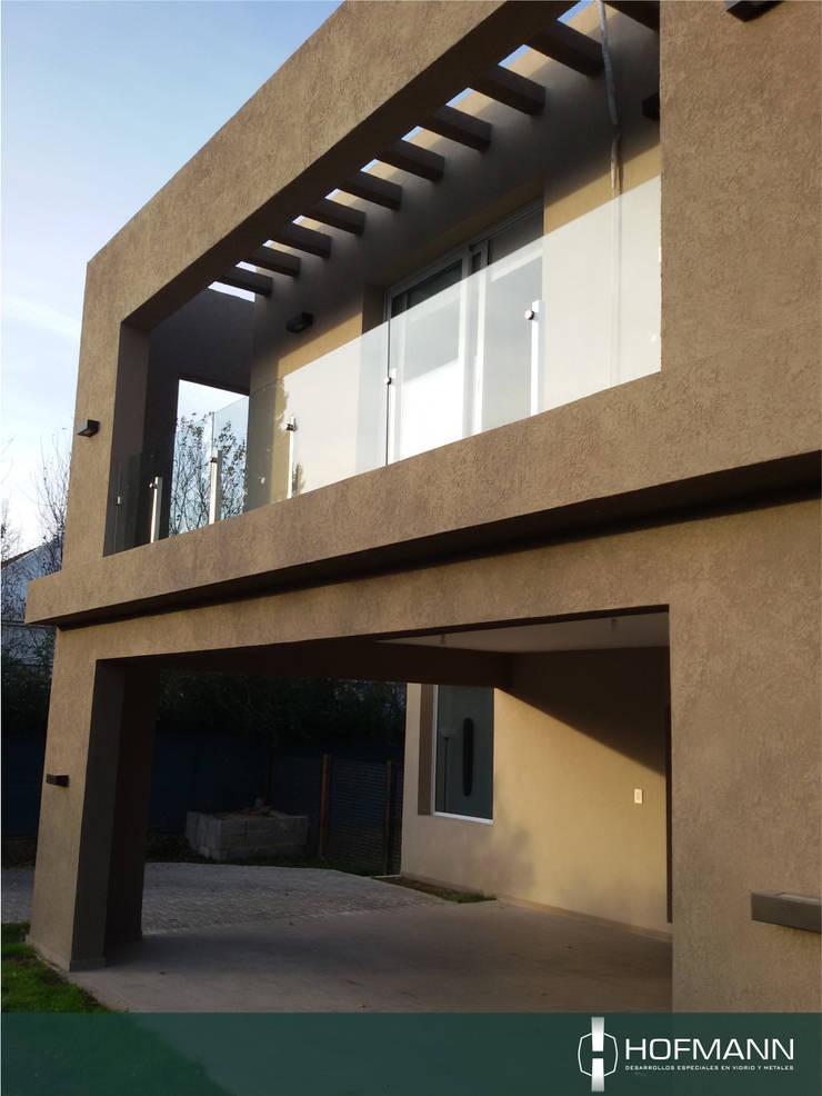BARANDA DE VIDRIO TEMPLADO MODELO POSTES Y BOTONES  DE ACERO INOXIDABLE: Terrazas de estilo  por HOFMANN - DESARROLLOS EN VIDRIO Y METAL,