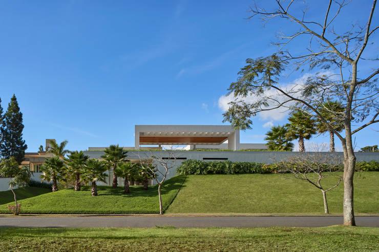 Vista frontal da rua, com destaque para os jardins e a grande cobertura que domina toda a composição.: Casas familiares  por Lanza Arquitetos