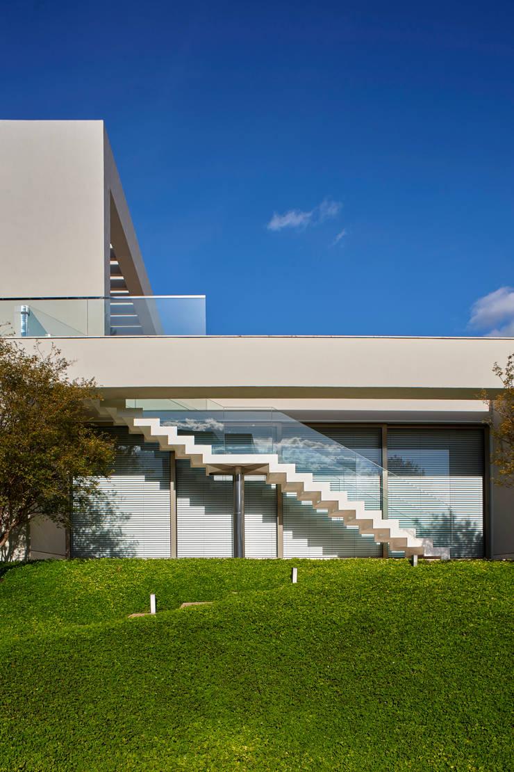 Escada de acesso ao Fitness: estrutura em metal, pisos de travertino, guarda-corpo de cristal temperado.: Casas  por Lanza Arquitetos