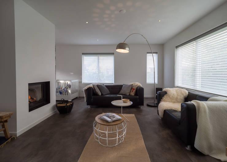 Modern & sfeervol interieur in vrijstaande woning:  Woonkamer door By Lilian